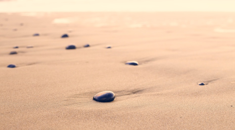 Sunset on series of black stones leading a path in the sand
